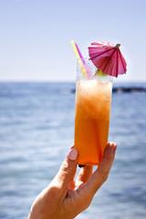 mano sosteniendo cocktail tropical en la playa
