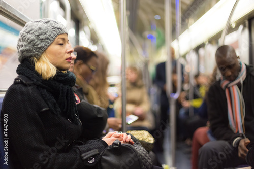 Woman napping on subway full of people. - 74474503