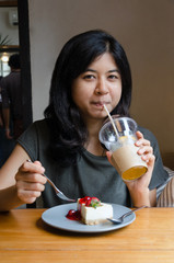 Woman drinking tea with strawberry cheesecake