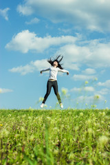 girl jumping in the field summer time