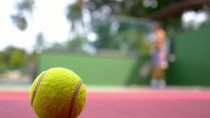 Tennis Ball on Court Close up with Tennis Player Background.
