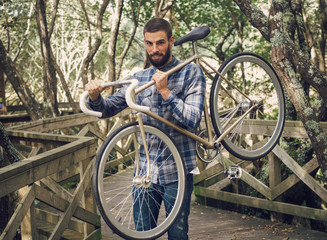 Hipster man holding his bicycle