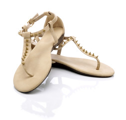 Beige sandals with studs on a white background