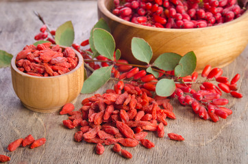Barberry and dry goji berries in bowls on wooden background
