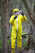 man in coveralls examining sample  in contaminated area