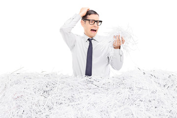 Shocked man looking at a pile of shredded paper