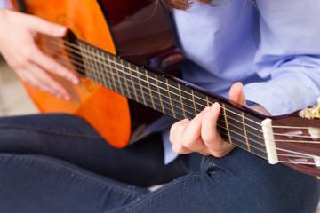 Closeup young girl playing guitar