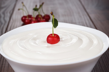 white bowl full of sour cream with cherry
