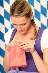 Frau im Dirndl bekommt ein Geschenk