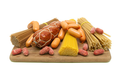 different types of pasta and sausages on a cutting board. white