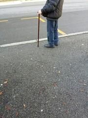 Persona anziana aspetta autobus alla fermata
