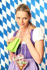 Frau im Dirndl mit Geschenktüte in der Hand