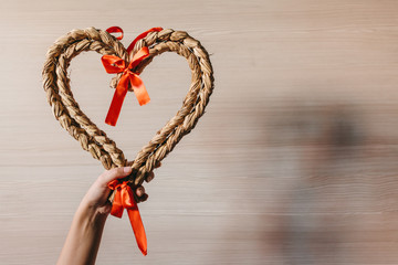 Woman Holding a Straw Heart Against a Wooden Background