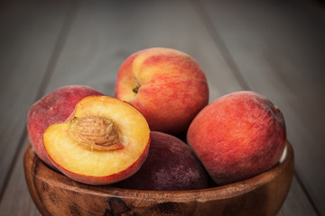 wooden bowl some fresh peaches on the table