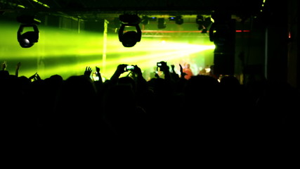 crowd of people filming using smartphones at party , silhouette
