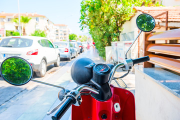red motorcycle stands on the sidewalk on the street
