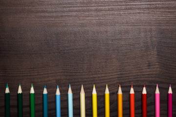 multicolored pencils over brown wooden table background