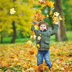 Little boy tossing leaves in autumn park