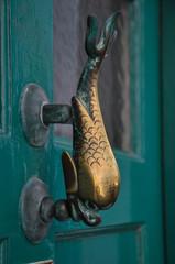 Traditional fish shape door knob on vintage door