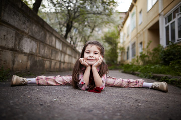 little pretty girl doing splits outdoors