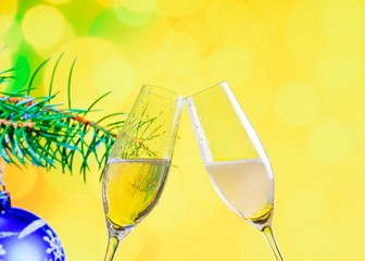 champagne flutes on christmas decoration yellow bokeh background