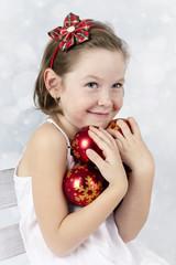 Little girl holding christmas balls
