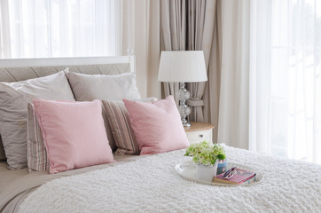 pink pillows on bed with tray of flower
