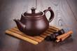 teapot with hot tea and cinnamon sticks