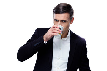 Handsome businessman drinking coffee over white background