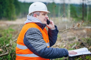 Forest engineer  with cell phone and documents in the forest
