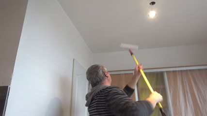 Painter man painting white wall with paint roller