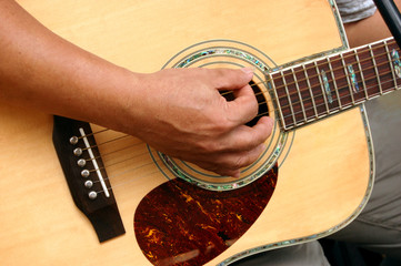 Hand playing an acoustic guitar