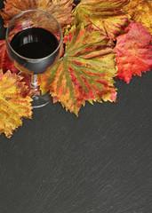 ardoise, feuilles de vignes et verre de vin