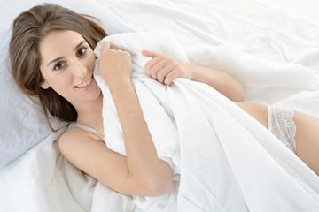 Frau liegt erholt im Bett