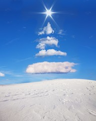 Christmas tree formed in the sky with clouds and sun, snowfield