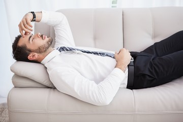 Businessman lying on couch after long day