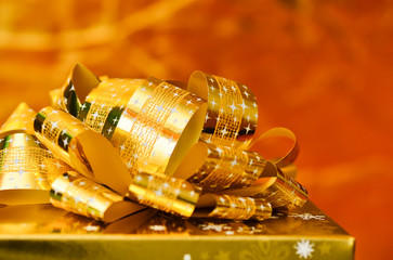 Golden gift box with gold ribbon.