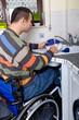 Rollstuhlfahrer beim Geschirr spülen