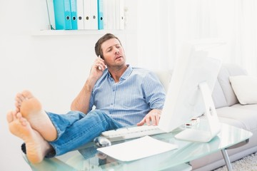 Businessman on the phone using his computer with his feet up