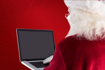 Composite image of santa claus uses a laptop