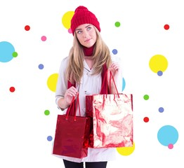 Composite image of pretty blonde holding shopping bags
