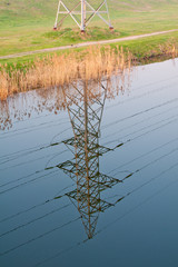 Tower high-voltage power line reflected in the water of the lake