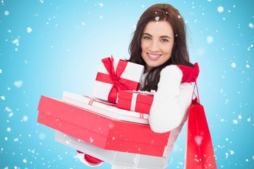 Joyful brunette holding christmas gifts and shopping bags