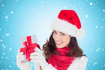 Composite image of excited brunette in santa hat showing gift