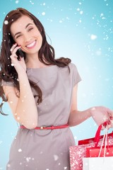 Smiling brunette with shopping bags on the phone