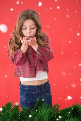 Composite image of festive little girl blowing over hands