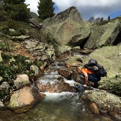Молодая девушка спортсменка пьет воду из горной речки