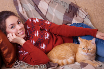 Young woman resting on sofa with a cat