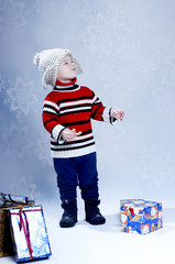 Happy small boy  in knitted hat and pullover with gift boxes, is