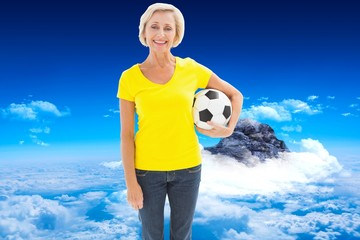 Mature blonde holding football smiling at camera
